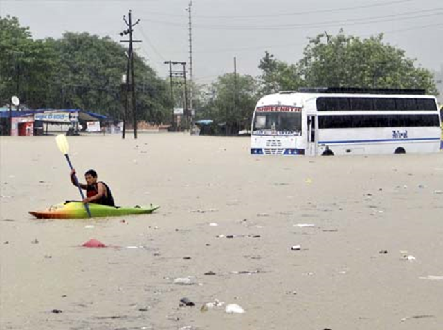 A man rows past a bus partly submerged in flood water in Rishikesh, Uttarakhand, 20 June 2013. Photo: AP