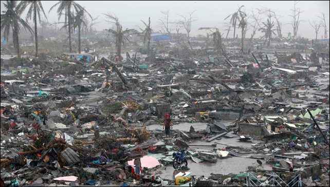 Survivors stand among debris and ruins of houses destroyed after Super Typhoon Haiyan battered Tacloban city in central Philippines, 10 November 2013. Photo: Erik De Castro / Reuters