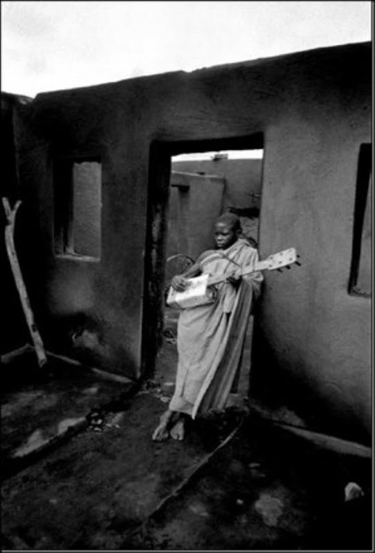 MASERU, Lesotho — A boy plays a guitar made from an oil can in the burned out ruins of his home during political violence, 1961.