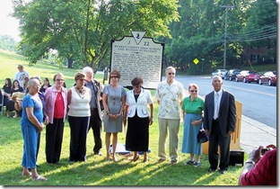 Former students posing in front of the marker after ceremony.