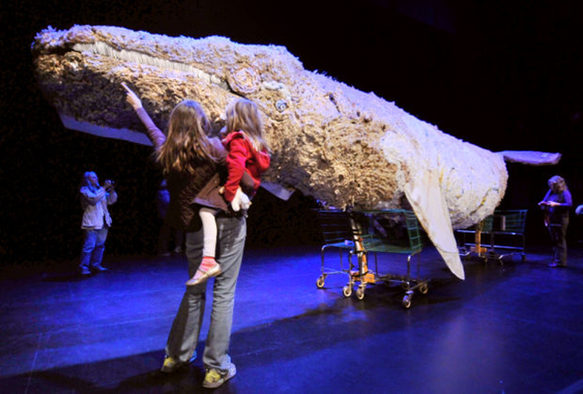 Heather Higinbotham points out to her daughter Scout, 7, details of a 32-foot-long replica of a gray whale made entirely of plastic bags, bottles and assorted garbage collected from our environment. The sculpture was on display on 17 October 2013 at the Dennison Theatre at the University of Montana. Photo: Michael Gallacher / Missoulian