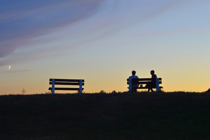 Silhouettes on bench with moon