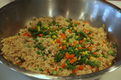 Cooked organic vegetables are added to the brown rice.