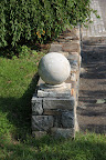 It looks just like one of the large, round, cement finials adorning the stone wall!
