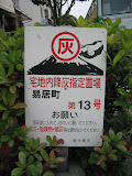 A common sign on the sidewalks of Kagoshima City, instructing residents and shopowners to bag the volcano ash they sweep up, and leave it by the sign for collection