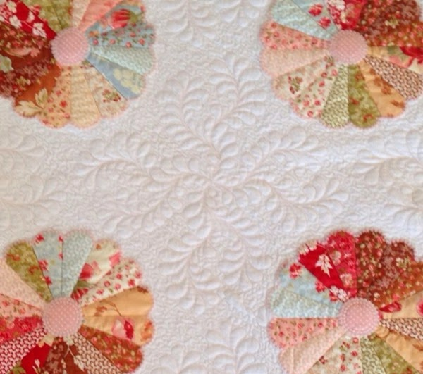 Feather motifs designed to fit the empty space in the quilt.