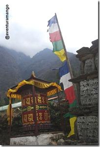 Roda de orações, bandeirinhas e pedras com orações budistas