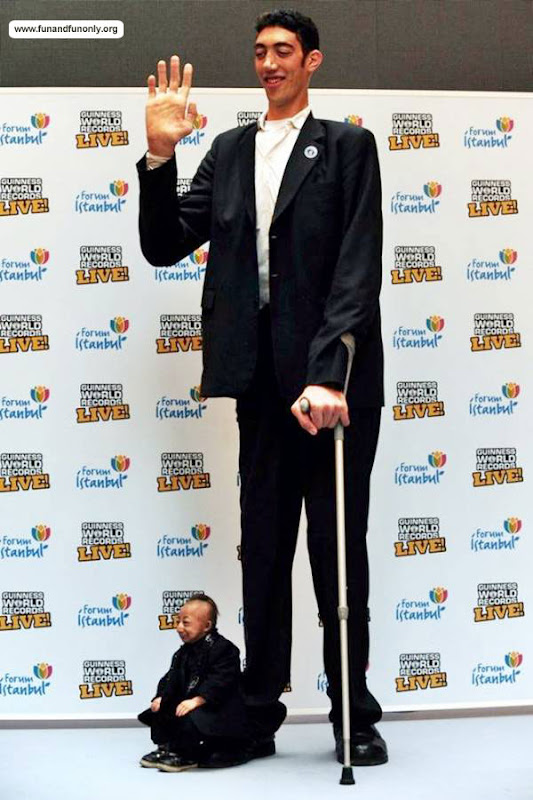 He Pingping of China (73 cm or 2 feet 5 inch, shortest man) stands next to Sultan Kosen of Turkey (246.5 cm or 8 feet 1 inch, Tallest man)