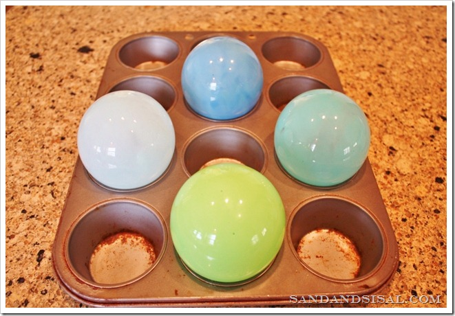 Place glass floats on cupcake pan to bake