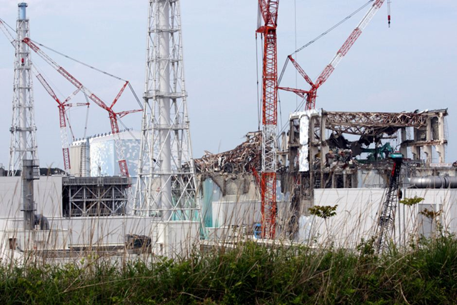 Construction cranes rise over the wrecked Fukushima nuclear plant. The Japanese government has ordered the operator of the Fukushima nuclear plant to freeze the soil around its crippled reactor buildings to stop groundwater seeping in and becoming contaminated. Photo: Tomohiro Ohsumi / AFP
