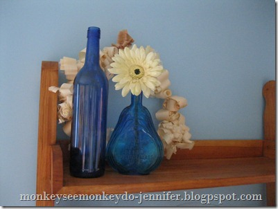 textured wreath display with blue glass bottles and flower