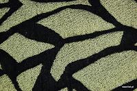 Tkanina obiciowa z efektem metalicznym. Motyw roślinny - liście. Czarna.