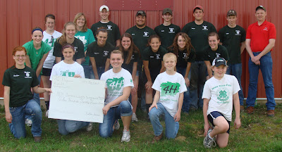 4-H members from both Benton county and 76 Progressives 4-H Club of Washington County  got to know each other better as they worked to plant five trees at the Benton County Fairgrounds in an effort to recover from last year's storm damage.  Washington County members who helped are in white and showcasing their Pioneer Grant check that helped complete this community service project.
