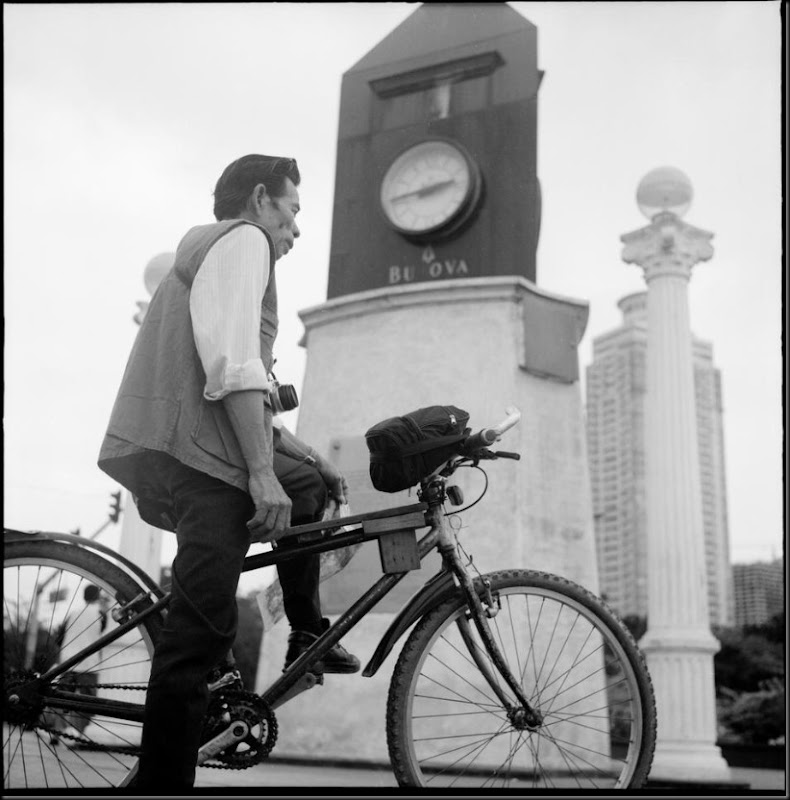 A photographer waits near the broken clock at Luneta Park for any potential customer asking for souvenir photos. Along with other resident photographers in the park, he uses film and refuses to use digital cameras because he cannot waste time and opportunities while trying to learn the new technology.