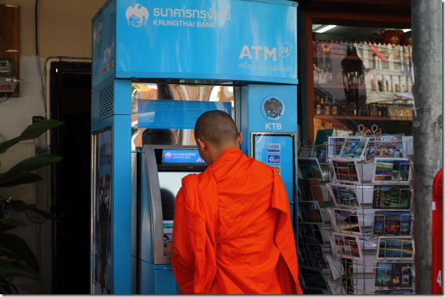 Buddhist monk uses a ATM at Chiang Mai, Thailand