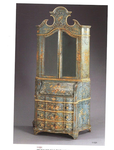 A bureau-cabinet painted pale blue and white and heavily decorated.  Some hidden details: it has mirrored doors and a bombe case that opens up to reveal secret drawers.