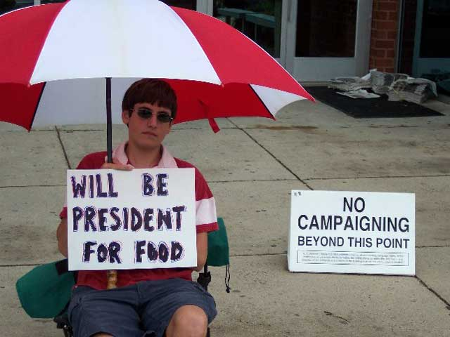 Boy holding sign 'Will Be President For Food'
