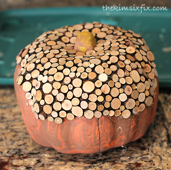 Gluing wood slices to pumpkin