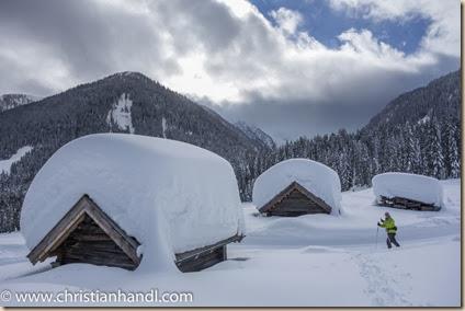 Holzhütten von viel Schnee bedeckt bei der Leitental Langlaufloipe