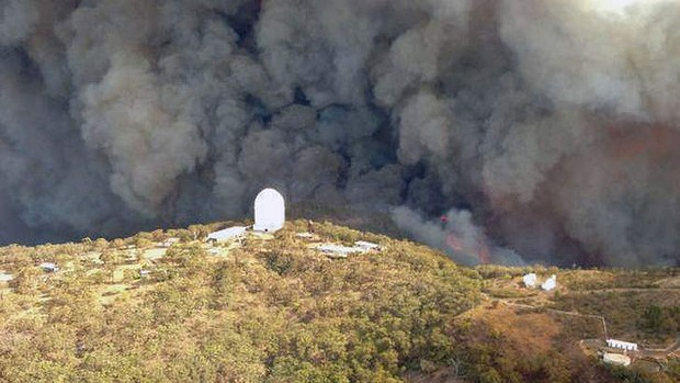 Aerial picture shows smoke billowing from an out-of-control fire raging towards the Siding Spring Observatory (centre), a remote global research facility in the Warrumbungle ranges about 500km north-west of Sydney, 14 January 2013. Photo: NSW Rural Fire Service