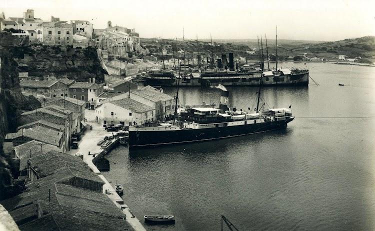 El REY JAIME II en atracado en Mahón. Ca. 1930. Al fondo se aprecian los buques de la Compañia Trasatlántica fondeados a disposición de desguaze. Postal.JPG