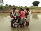 LOCAL PEOPLE HELPING TO CROSS THE BIKE OF MISSIONARY.JPG