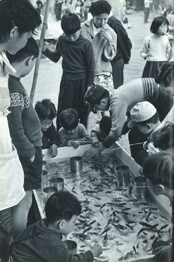 Japanese schoolchildren catching fish from a little pool. Could they be more adorable?