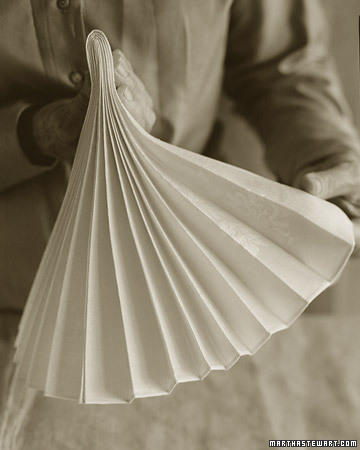 A napkin in an accordion fold, also known as a stemware fold, is an artful accent to the holiday table. Fold the pleats in half as shown, insert the bottom into a glass, and then fan out the top pleats.
