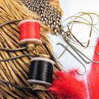 Fot.1. Materiały potrzebne do wykonania muszki: Haczyk 4xlong. Szyjne pióra koguta o ubarwieniu typu badger na skrzydełka i jeżynkę. Czerwona wełna na tułów, złota płaska lameta. Miękkie czerwone piórko na ogonek. Pióra jungle cock. Czerwona i czarna nić wiodąca.