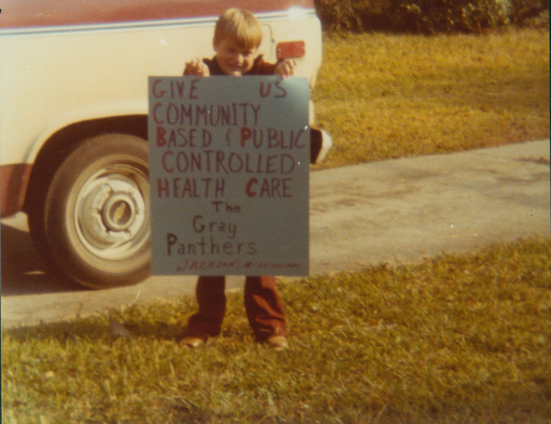 Bobby Smith holds a Gray Panthers sign before a demonstration. Undated.