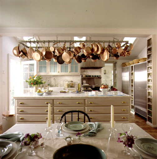 Martha likes to hang her pots and pans from hooks on an overhang. This frees up storage space in her kitchen while also adding a chandelier-like element to the room.