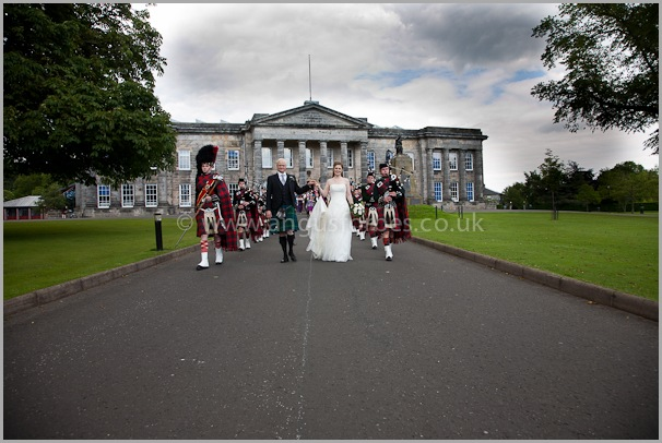 bride and groom with pipe band in scotland