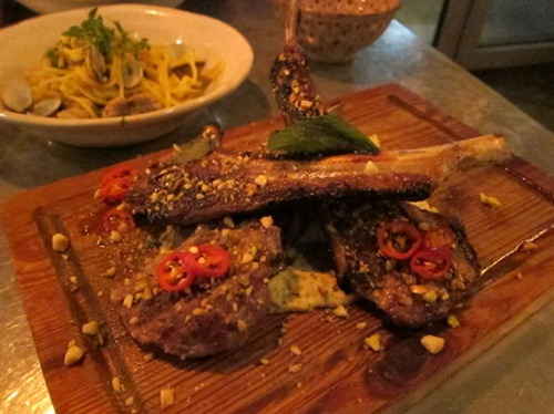 Bone in grilled lamb chops, served with creamy artichoke and mint sauce, roasted nuts, chilli and fresh mint