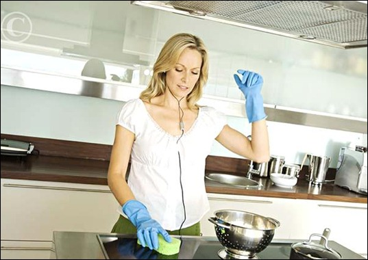 young_woman_cleaning_kitchen_while_listening_to_ky149007