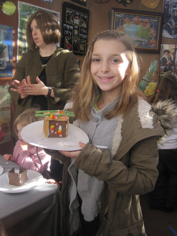 One of our younger participants with her edible gingerbread sukkah