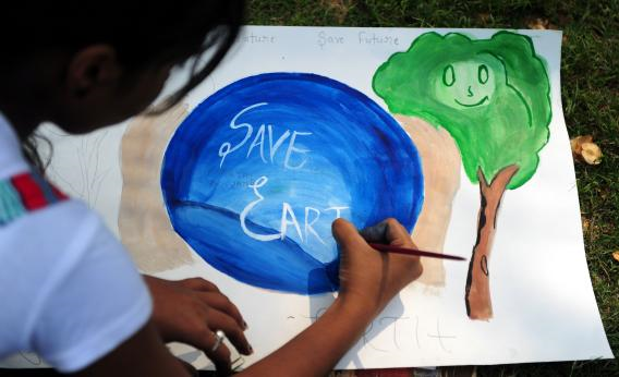 An Indian child paints during an awareness event organized by the Aakalpan Artist Society commemorating Earth Day in Allahabad. Photo: Sanjay Kanojia / AFP / Getty Images