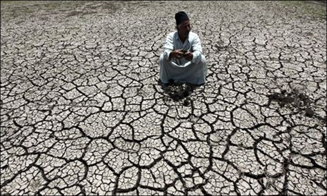 An Egyptian farmer shows the dryness of the land due to drought in a farm formerly irrigated by the river Nile. Photo: Mohamed Abd El Ghany / Corbis