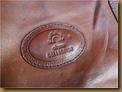 Tas kulit Charm - logo