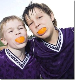 two boys with orange wedges