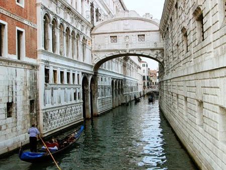 Gondoleiro passa próximo à Ponte dos Suspiros em Veneza