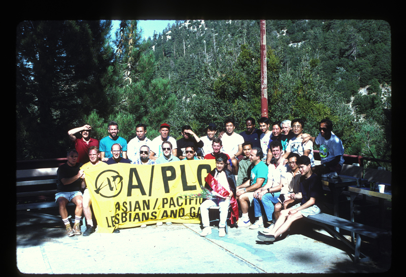 Asian/Pacific Lesbians and Gays (A/PLG) retreat group picture with banner. Undated.