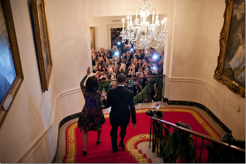President Barack Obama and First Lady Michelle Obama descend the Grand Staircase to greet guests at a holiday reception in the Grand Foyer of the White House, Dec. 15, 2011. (Official White House Photo by Pete Souza)<br /><br />This official White House photograph is being made available only for publication by news organizations and/or for personal use printing by the subject(s) of the photograph. The photograph may not be manipulated in any way and may not be used in commercial or political materials, advertisements, emails, products, promotions that in any way suggests approval or endorsement of the President, the First Family, or the White House.