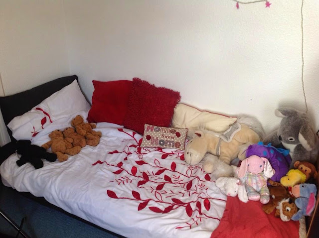 child's bed with cuddly toys and bears