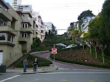 A part of Lombard Street where cars are driving downhill on a windy road