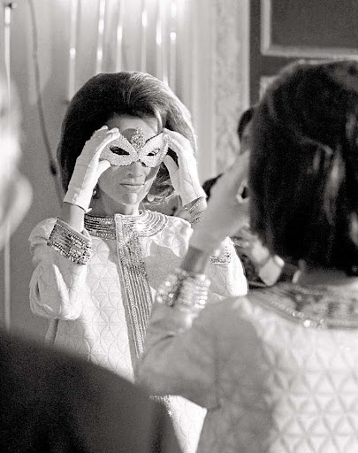 Princess Lee Radziwill adjusts her mask.
