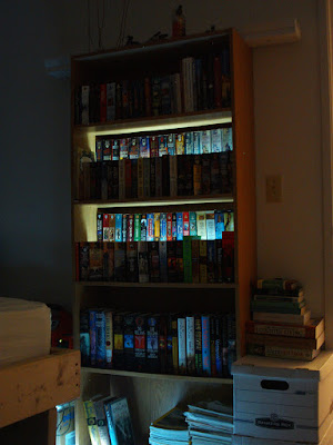 back-lit bookshelf risers at night.