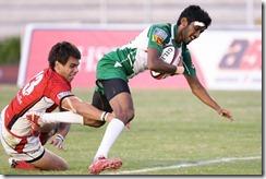 2012-Sri Lanka v Singapore. Lankan fullback Rizah Mubarak gets by Singapore's Nicholas Groen