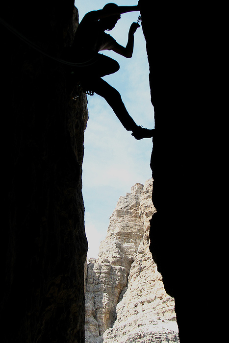 Trad climbing in a perfect chimney on the Dulfer route up the Cima Grande di Lavaredo, Italy.