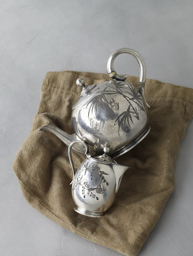 A silver-plate teapot and creamer from the late 1880s; bright-cut patterns decorate both sides of the hollowware.