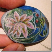 smooth beach rock with a white water lily and silver decoration